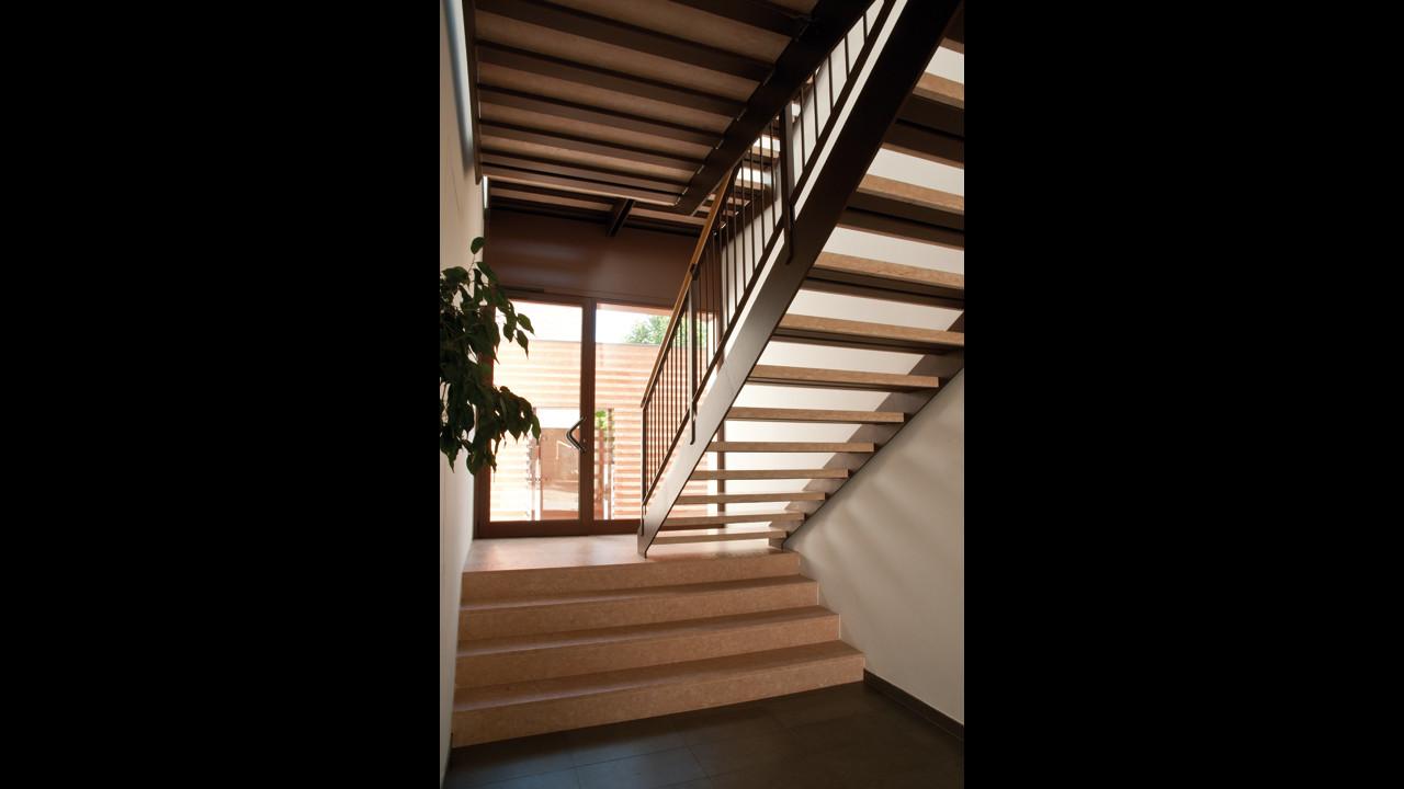 Casa M10 Foto del vano scala comune al piano terra. Struttura in ferro verniciato e rivestimento in marmo rosa di Verona.