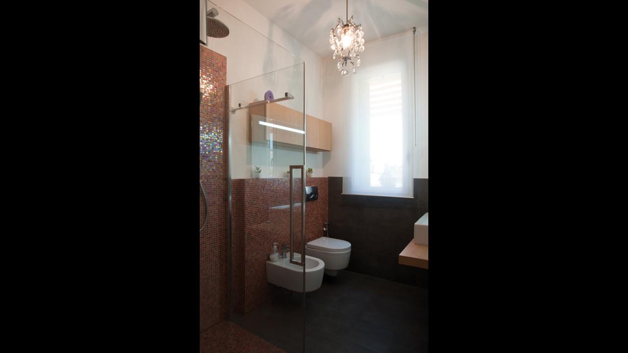Casa M10 Foto del bagno al piano terra della villetta. Pavimento in gres porcellanato e rivestimento in mosaico vitreo Sicis Iridium Dahlia.