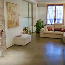 Casa B04 Foto del soggiorno. Particolare della parete decorativa in mattoni di laterizio di recupero e del pannello vetrato scorrevole.