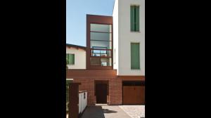 Casa M10 Foto esterna. Veduta dell'ingresso principale attestato sul vano scala comune.