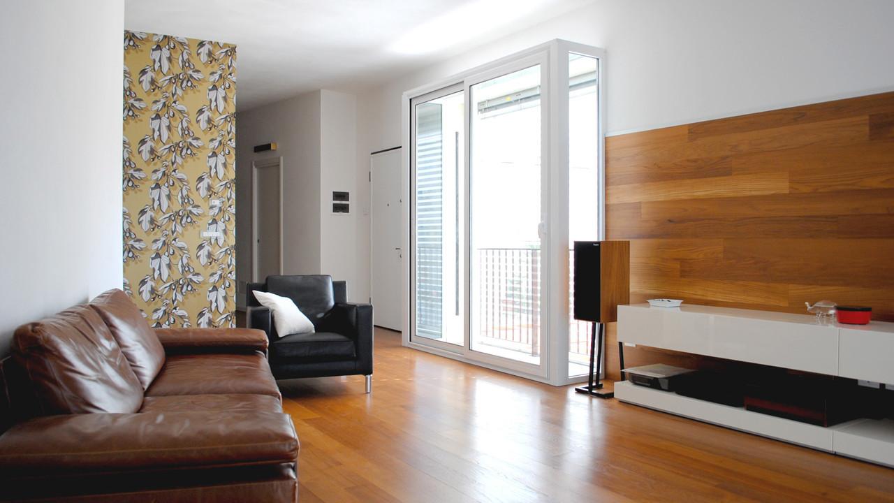 Casa M10 Foto del soggiorno. Pavimento e boiserie continuo in listoni di teak. Carta da parati a fondo dorato. Bow-window.