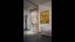Casa B04 Foto del soggiorno. Particolare della parete decorativa in mattoni di laterizio di recupero.