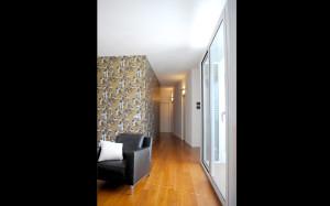 Casa M10 Foto della zona d'ingresso con bow-window dell'alloggio al piano primo. Pavimento in listoni di teak. Carta da parati a fondo dorato.