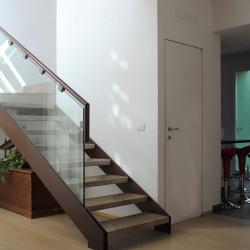 Casa M10 Foto del vano scala della villetta in ferro e pietra. Pavimento in listoni di legno.