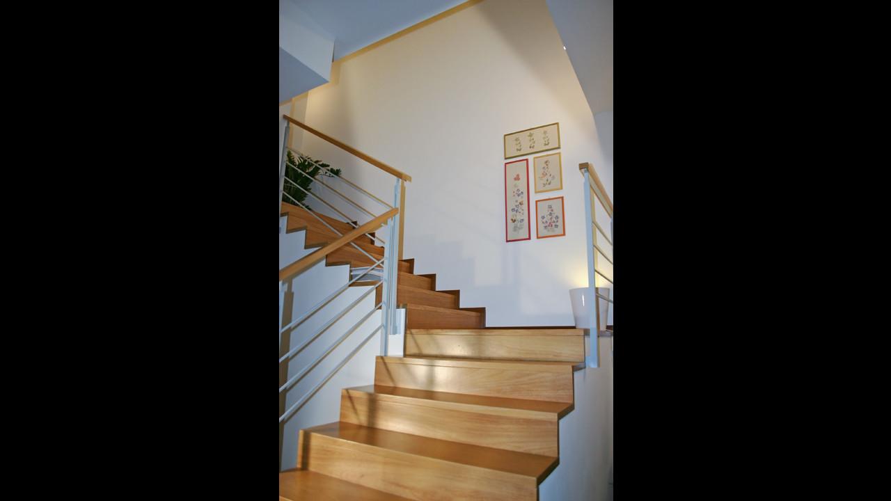 Casa B04 Foto della scala con rivestimento continuo in legno.